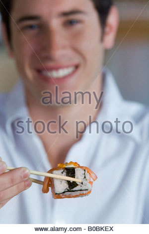 Junger Mann Sushi mit Stäbchen zu essen, Lächeln, Porträt differenzielle Fokus - Stockfoto