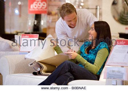 Junges Paar mit Stoffmustern im Shop, Lächeln einander an - Stockfoto