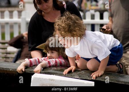 zwei Kleinkinder kniend durch einen Springbrunnen - Stockfoto