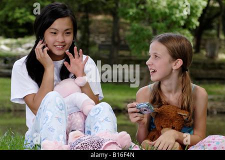 Stock Foto von einem Mädchen auf einem Handy zu sprechen, während ein anderer macht sich bereit zu fotografieren - Stockfoto
