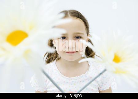 Mädchen hinter Blumen, lächelnd in die Kamera, Porträt - Stockfoto