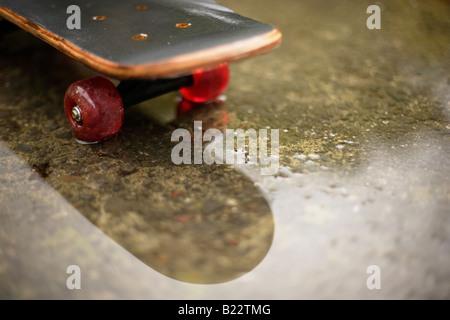 Skateboard in Pfütze - Stockfoto