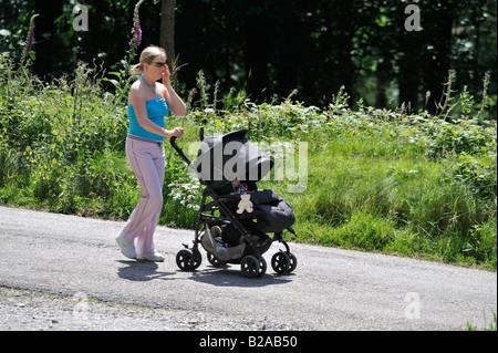 Mutter drängt Kind im Buggy heraus für einen Spaziergang entlang der vielen schönen und interessanten Wege des Upper - Stockfoto