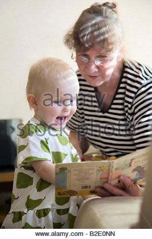 Ältere Frau, die ein Bilderbuch an ihre Enkelin - Stockfoto