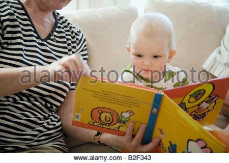 Eine ältere Frau, die ein Bilderbuch an ihre Enkelin Mitte Schnittansicht - Stockfoto