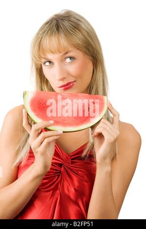 Süße blonde Mädchen im roten Kleid und roten Lippen mit einem Stück Wassermelone Gesicht - Stockfoto