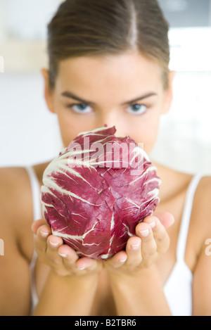 Frau hält einen Kopf Radicchio-Salat, teilweise verdeckt Gesicht, Blick in die Kamera - Stockfoto