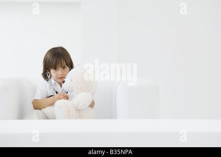 Kleiner Junge spielt Arzt mit Teddybär, mit Stethoskop - Stockfoto
