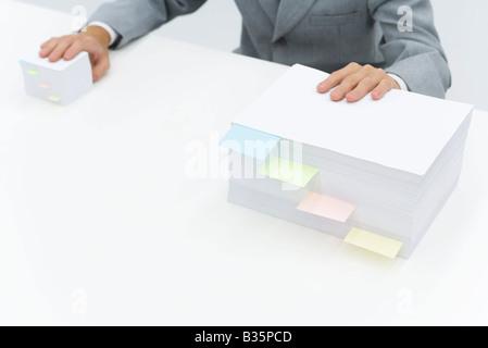 Stapel von Papier mit Kleber Noten teilt sie, Mann legte eine Hand auf jeden Stapel - Stockfoto