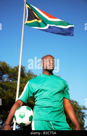 13MA-023 © Monkeyapple aFRIKA Sammlung großer Lager!  Fußballspieler mit Ball unter südafrikanischer Flagge posiert - Stockfoto