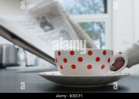 Person mit Tee und Zeitung - Stockfoto