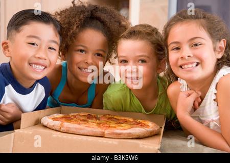 Vier kleine Kinder im Haus mit Pizza lächelnd - Stockfoto