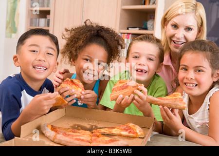 Vier kleine Kinder im Haus mit Frau Essen Pizza lächelnd - Stockfoto