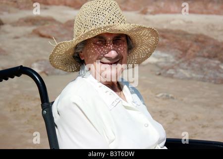 Eine alte Dame saß in einem Rollstuhl am Strand - Stockfoto