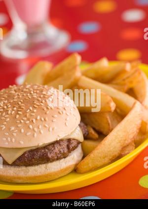 Cheeseburger in einem Sesam Brötchen mit klobigen Chips - Stockfoto
