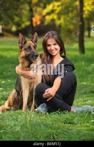 Lächelnde Teenager umarmen einen Hund - Stockfoto