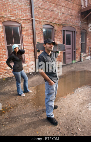 Junge Hispanic Mann in Gasse mit Skateboard, Frau im Hintergrund - Stockfoto