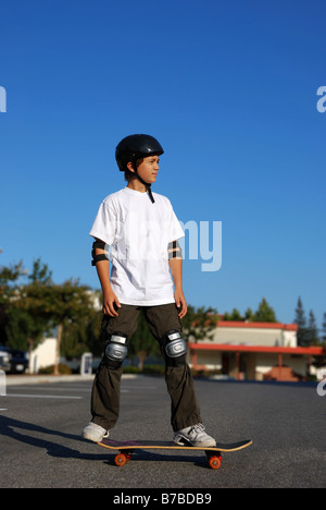 Junge stand auf einem Skateboard in einen Nachmittag in der Sonne mit blauem Himmel im Hintergrund - Stockfoto