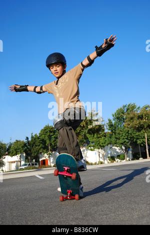 Junge tun Stunts auf einem Skateboard in der Nachmittagssonne mit blauen Himmel im Hintergrund - Stockfoto