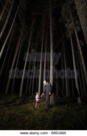 Mann im Anzug mit kleines Mädchen stehen neben unheimliche Bäume in der Nacht, Cypress Hills, Saskatchewan und Gasmaske - Stockfoto