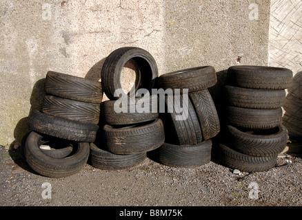 Reifen gestapelt gegen eine Garagenwand. - Stockfoto