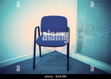 Blauer Stuhl in einer Ecke neben einer Jalousie - Stockfoto