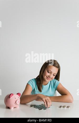 Mädchen mit Sparschwein und Münzen - Stockfoto