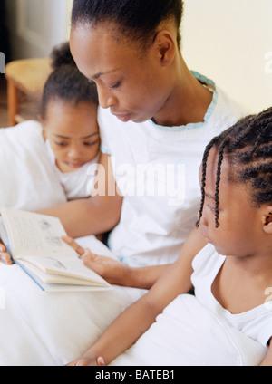 Bettlektüre. Motherreading ein Buch ihrer vier-jährige Tochter (Atleft) und fünf Jahre alten Sohn vor dem Schlafengehen. - Stockfoto