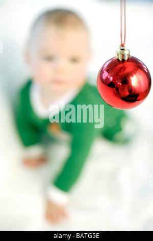 Baby Junge eine Weihnachtskugel betrachten. Er ist neun Monate alt. - Stockfoto
