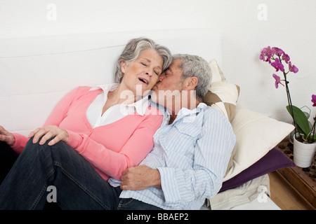 Ein senior Mann und ältere Frau zusammen auf einer Couch liegen - Stockfoto