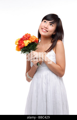 Junge Frau trägt weißes Kleid und hält Blumenstrauss - Stockfoto