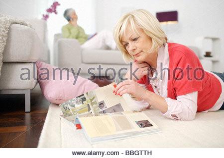 Ältere Frau zu Hause lesen mit Frau am Telefon Hintergrund Magazin - Stockfoto