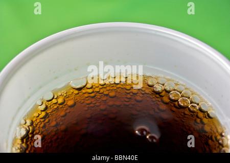 Coca Cola Bläschen im weißen Glas am grünen Tisch serviert. Kälte, Getränk, Getränke, Glas, Coca Cola, Coke, Pepsi, - Stockfoto