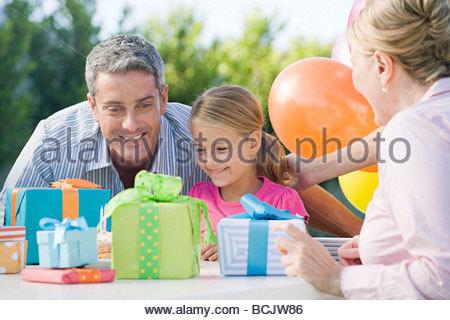 Kleine Mädchen und ihr Vater betrachtet man Geburtstag präsentiert - Stockfoto