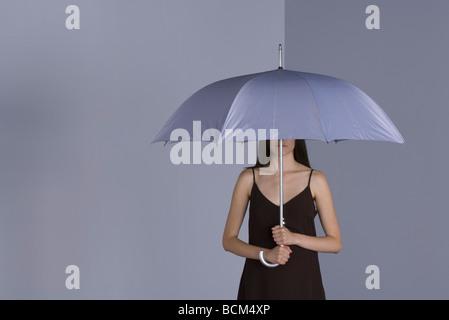 Frau stehend unter Dach, Gesicht teilweise verdeckt - Stockfoto
