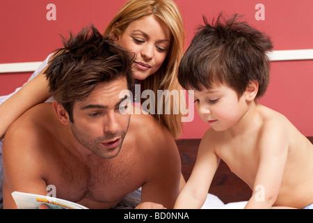 paar junge eine Geschichte im Bett zu lesen - Stockfoto