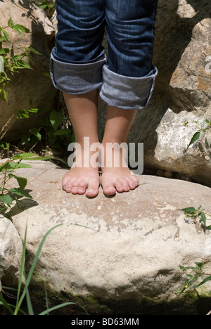 Frau, die barfuß auf den Felsen am Fluss - Stockfoto