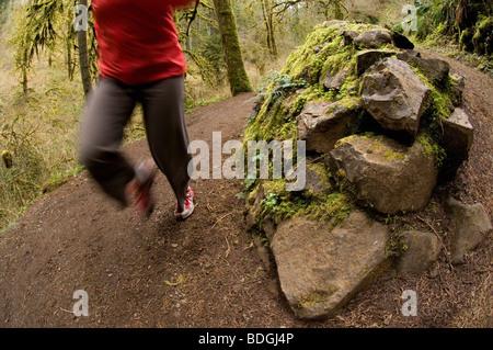 Eine Frau läuft ein Wanderweg durch einen grünen, moosigen Wald in Silver Falls State Park, Oregon, USA. - Stockfoto