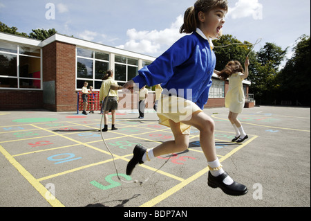 Schulmädchen überspringen in einer Grundschule Spielplatz im Vereinigten Königreich. - Stockfoto