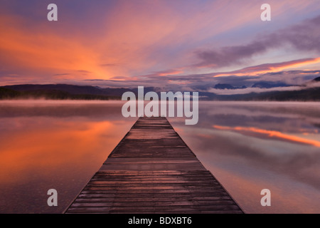 Sonnenaufgang über dem Lake McDonald, Glacier National Park Deck; aus Holz; Boot; Plattform; - Stockfoto