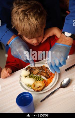 Erwachsenen mit blauen Latex Handschuhen schneiden das Essen für ein junges Kind Schule Abendessen in einer Grundschule, - Stockfoto
