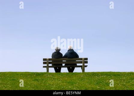Älteres Ehepaar sitzt auf einer Bank auf dem Deich - Stockfoto