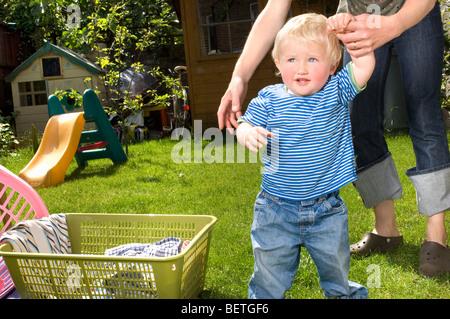 Frau helfende Kleinkind zu Fuß - Stockfoto