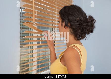 Junge Frau, Blick aus dem Fenster durch Vorhänge - Stockfoto