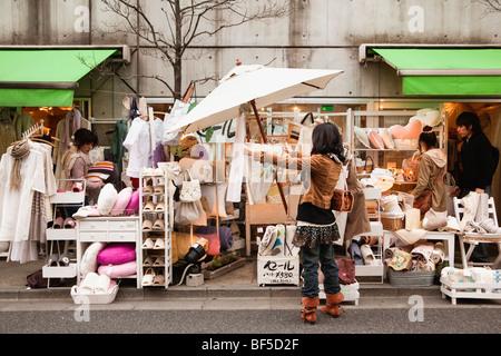 Eine junge Frau blickt auf einige Haushaltswaren in einem Shop in Shimokitazawa, Tokyo, Japan - Stockfoto