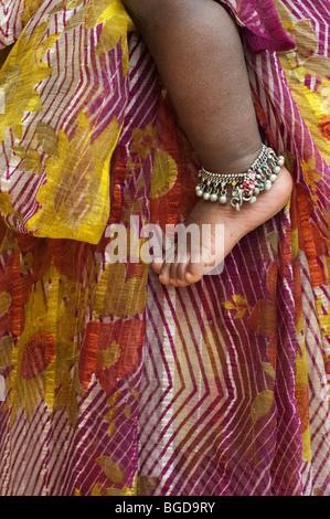 Indische Babys nackten Fuß tragen ein Fußkettchen gegen Mütter gestreift gemusterte sari - Stockfoto