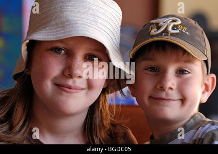 Porträt eines jungen Mädchens mit Sommersprossen und ein Hut und ein kleiner Junge trägt eine Schirmmütze - Stockfoto