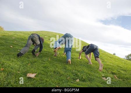 drei Jungs, ein Rennen auf einem grasbewachsenen Hügel klettern, auf allen Vieren - Stockfoto