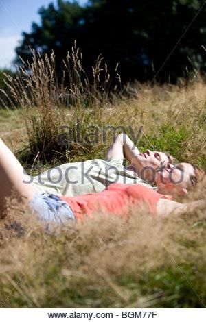 Ein junges Paar auf dem Rasen liegen, relaxen - Stockfoto