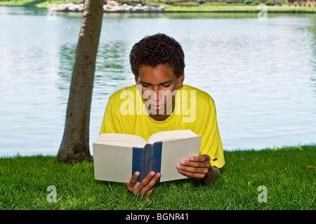 16-17 Jahre alten Teenager Hispanic/African American junge junge Mann entspannend entspannt lesen im Park unter - Stockfoto